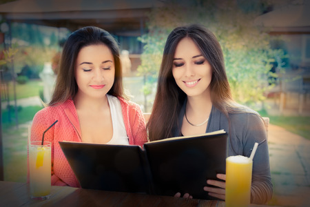 Young women at a restaurant deciding what to order photo