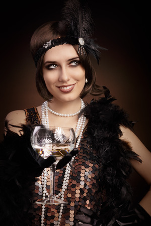 Portrait of a flapper girl with a glass of champagne photo