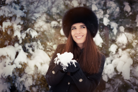 Stylish woman in wintertime making a snowball photo