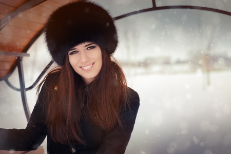 Stylish woman in wintertime wearing big fur hat photo