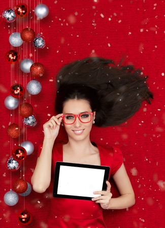Beautiful smiling woman surrounded by Christmas decorations holding a tablet PC photo