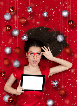 Beautiful amazed woman surrounded by Christmas decorations holding a tablet PC photo