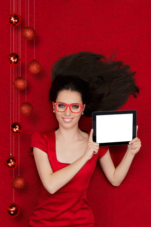Beautiful smiling woman in Christmas decor holding a tablet PC