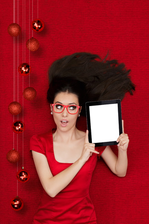 d cor: Beautiful amazed woman in Christmas decor holding a tablet PC