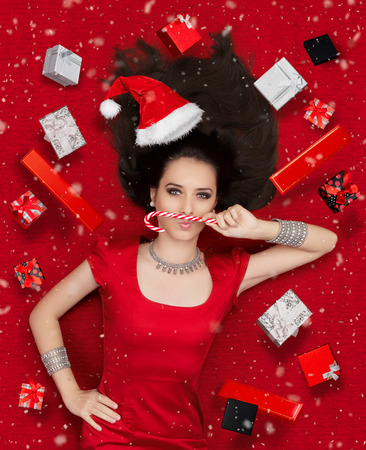 jewel box: Beautiful expressive woman in sweet Christmas fantasy portrait with lollipop and gifts Stock Photo