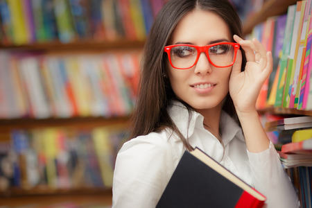 Portrait of a woman with red eyeglasses holding a book in a library Archivio Fotografico
