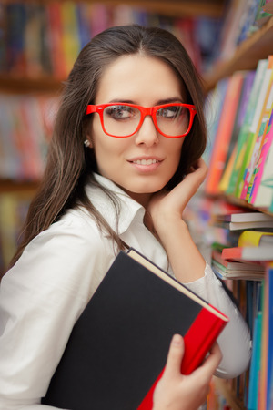 freshmen: Portrait of a woman with red eyeglasses holding a book in a library Stock Photo