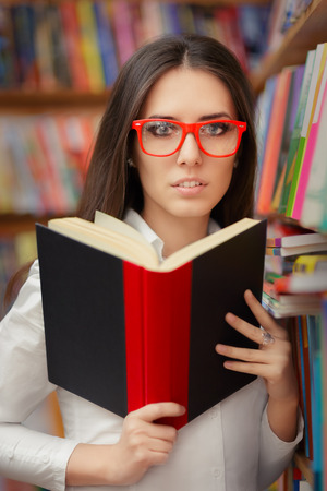 freshmen: Portrait of a woman with red eyeglasses reading a book in a library