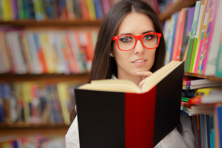 Portrait of a woman with red eyeglasses reading a book in a library