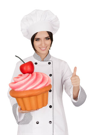 bake sale sign: Portrait of a professional cook approving a giant baked and decorated muffin