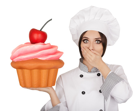 Portrait of a professional cook surprised by the giant baked and decorated muffin Stock Photo - 34598590