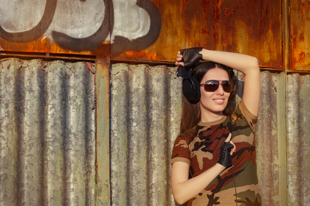 Portrait of a happy girl listening to music in a military fashion outfit
