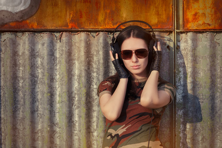 rebellious: Portrait of a happy girl listening to music in a military fashion outfit