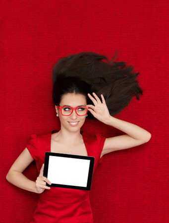 Beautiful smiling woman in red decor holding a tablet PC photo