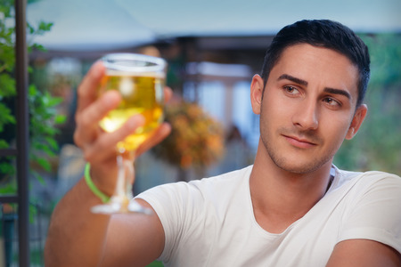 pilsner glass: Young Man Rising a Glass in a Bar Stock Photo