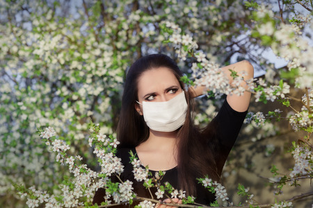Allergic woman surrounded by seasonal flowers wearing a protective mask