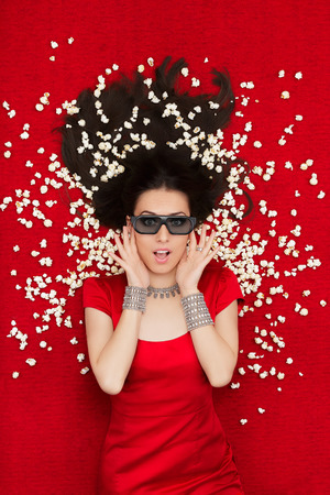 Amazed woman on red carpet watching a tridimensional film surrounded by popcorn photo