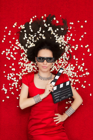 Beautiful woman on red carpet watching a tridimensional film surrounded by popcorn