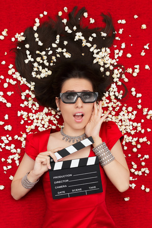 Amazed woman on red carpet watching a tridimensional film surrounded by popcorn