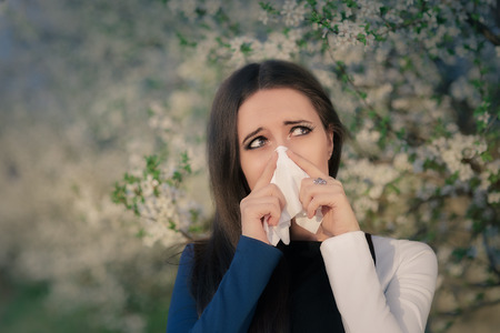 with pollen: Portrait of a sick woman blowing her nose