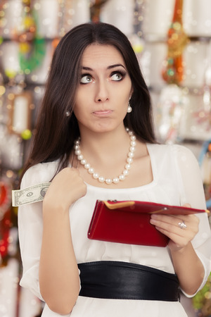 Portrait of a funny girl looking for money in her purse photo