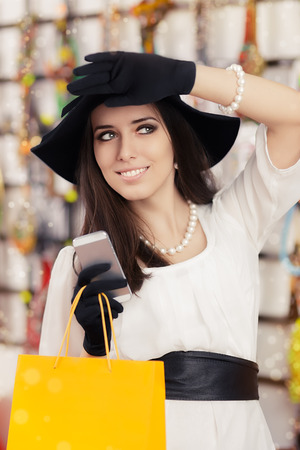 Portrait of a young elegant girl with shopping bags with Smartphone photo