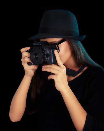 fashion shoot: Portrait of a cool with hat and glasses girl holding a DSLR camera