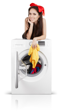 Young happy housewife smiling while doing laundry photo