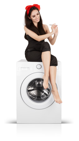 manicurist: Young bored housewife spending time doing her manicure on a washer Stock Photo