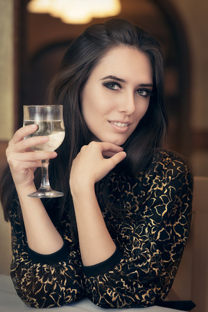 Portrait of a classical beauty toasting with a glass of champagne photo