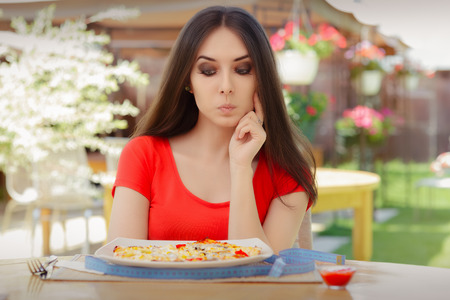 plato del buen comer: Mujer joven que piensa en comer pizza en una dieta Foto de archivo