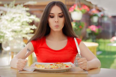 ni�a pensando: Mujer joven que piensa en comer pizza en una dieta Foto de archivo