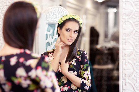 Beautiful Girl Looking in the Mirror and Trying on Floral Dress photo