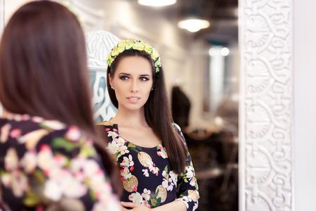 ropa de verano: Muchacha hermosa que mira en el espejo y El intentar en el vestido floral