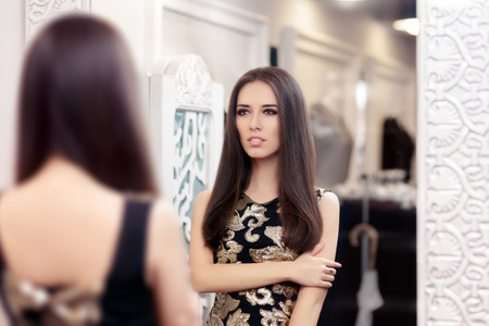new look: Beautiful Girl Looking in the Mirror and Trying on an Elegant Dress