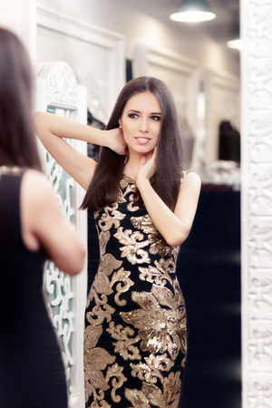 Beautiful Girl Looking in the Mirror and Trying on an Elegant Dress photo