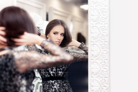 Beautiful Girl in Black Lace Dress Looking in the Mirror photo