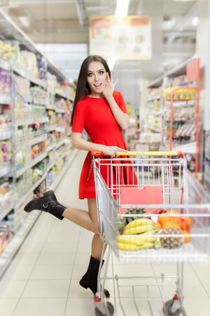 shopping buggy: Surprised Woman Shopping  at The Supermarket Stock Photo
