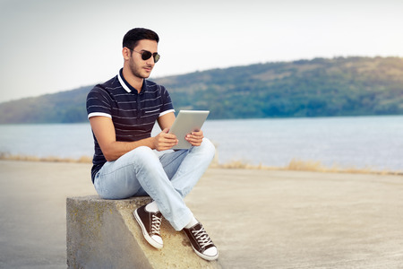 Young Man with Sunglasses and Tablet by the Water Stock Photo