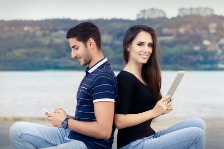 media gadget: Happy Couple Checking their Smartphone and Tablet Stock Photo