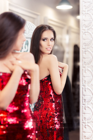 Beautiful Girl in Red Sequin Dress Looking in the Mirror photo