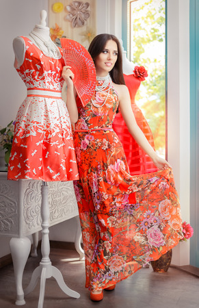 Woman in Long Red Floral Dress in Fashion Store Standard-Bild