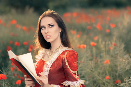 vestido medieval: Hermosa princesa Lectura de un libro en el paisaje floral del verano