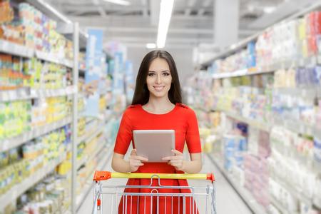 tiendas de comida: Mujer feliz con la tableta de compras en el supermercado