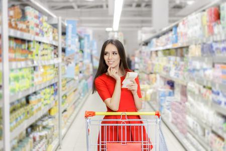 carro supermercado: Pizca de la mujer lista de la compra en el supermercado Foto de archivo