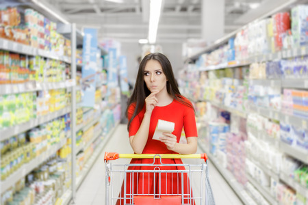comprando: Mujer curioso en el supermercado con el carro de la lista