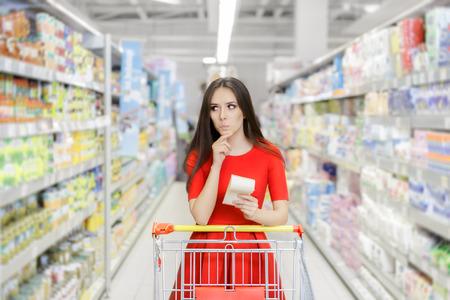 Nieuwsgierig vrouw in de supermarkt met de Shopping List
