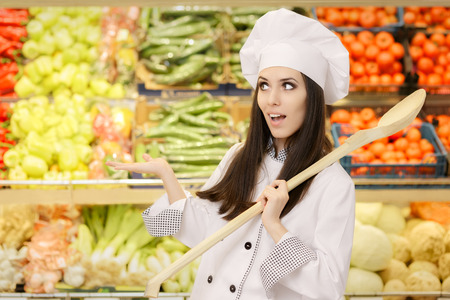 local supply: Funny Lady Chef with Big Spoon Presenting Fresh Vegetables