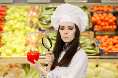 food supply: Concerned  Lady Chef Inspecting Vegetables with Magnifying Glass