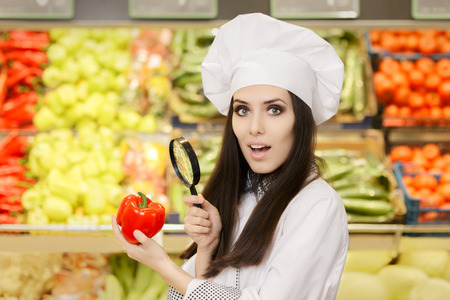 intrigued: Funny Lady Chef Inspecting Vegetables with Magnifying Glass